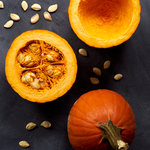 Whole and halved sugar pumpkin with seeds on a dark chalkboard background